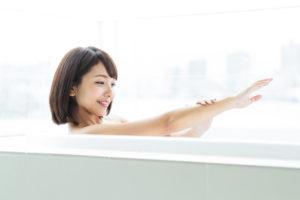 湯舟に浸かって二の腕のぶつぶつを治す女性