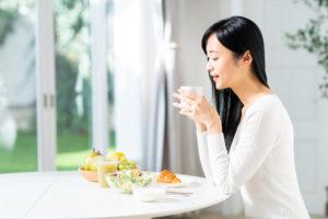 ウェストを絞る朝食を摂る女性