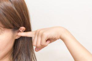 耳つぼをマッサージする女性